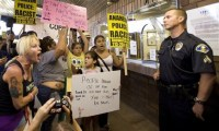 Protestors haranguing Anaheim policeman.